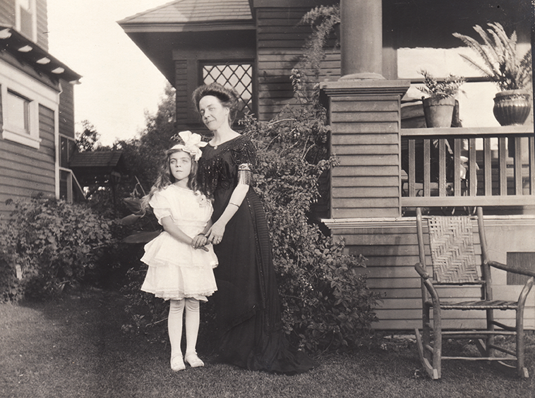 Nine-year-old Ursula and her mother, Clara Uphoff Cheshire, in front of their LA home. I love Clara's dress!